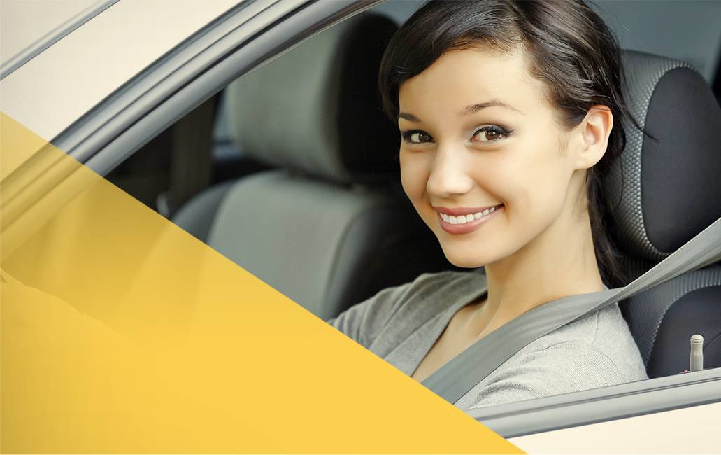 Woman driving in car with seatbelt on, smiling