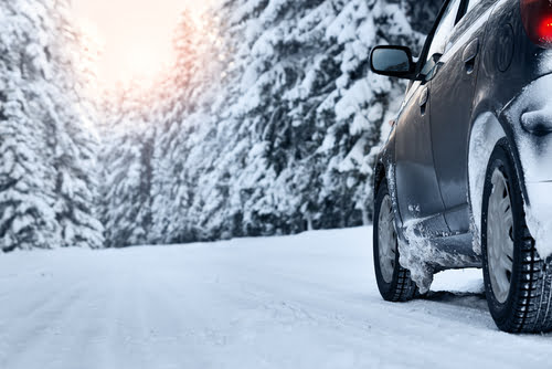 Image of car with winter tires driving on a snow cover road