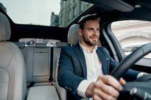 Young businessman (30s) driving car
