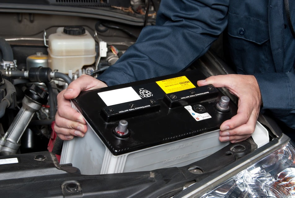 auto technician installing a new car battery into vehicle
