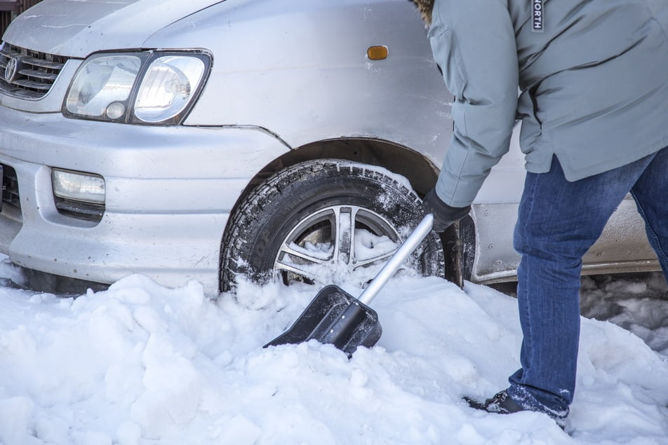 man using snow shovel to dig out car