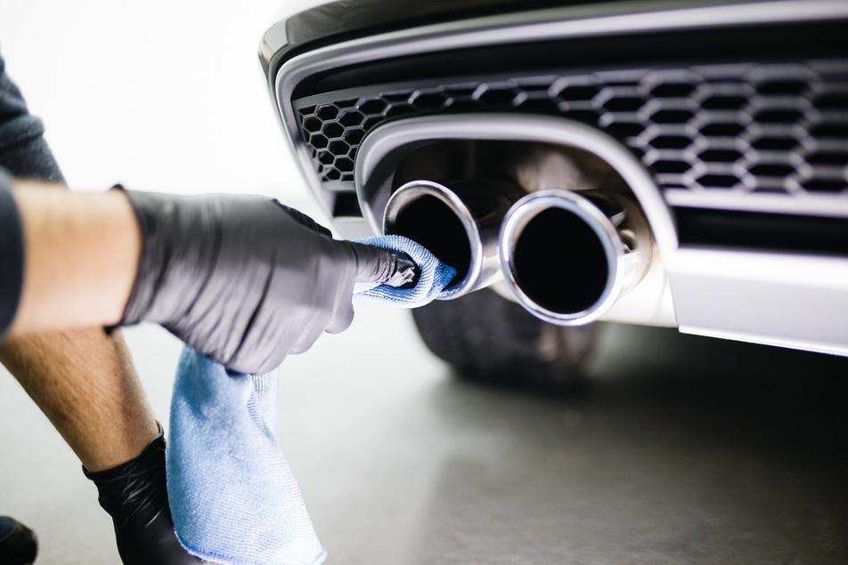 auto mechanic cleaning car exhaust system
