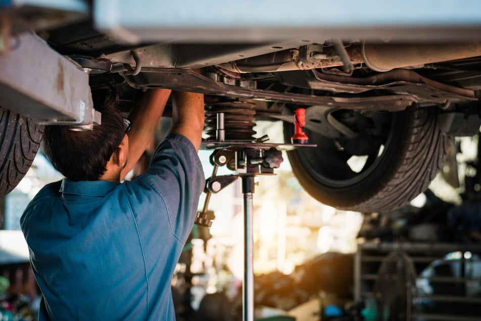 mechanic repairing vehicle's suspension system