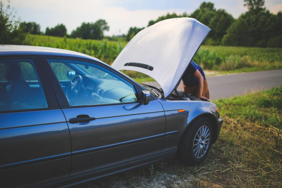 man checking car battery issue during summer