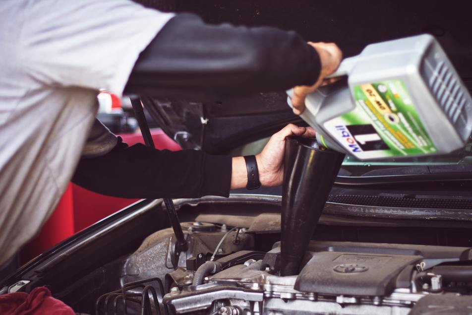 mechanic switching engine oil in car for summer