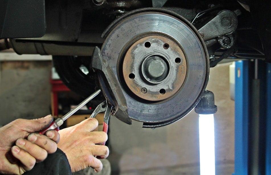 mechanic repairing worn brake pad