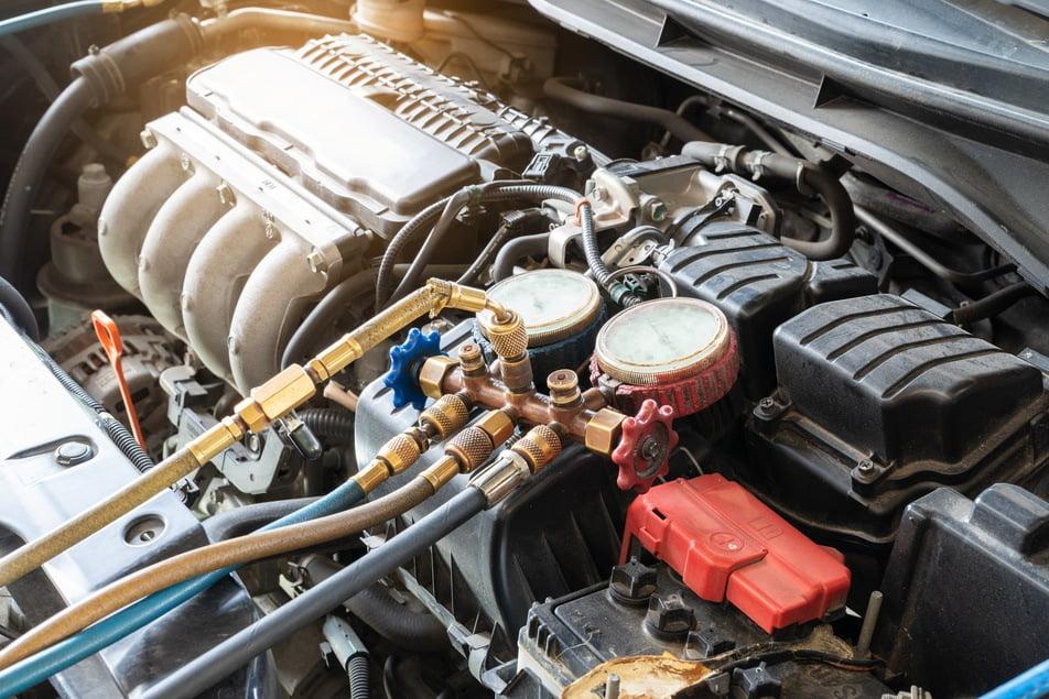 mechanic repairing vacuum leak in engine